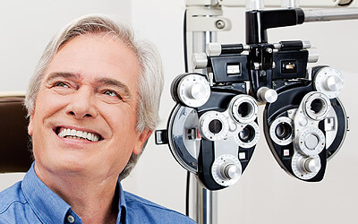 Man smiling while sitting next to eye exam equipment