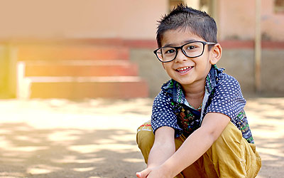 Boy sitting on the ground with glasses on smiling